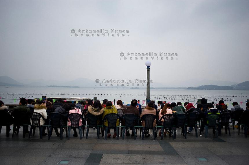 Hangzhou, Cina, 7 Marzo, 2015. Gente seduta sul lungo lago al tramonto.<br /> People sitting on the terrace of West Lake in hangzhou