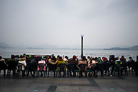Hangzhou, Cina, 7 Marzo, 2015. Gente seduta sul lungo lago al tramonto.<br /> People sitting on the terrace of West Lake in hangzhou