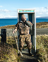 Outdoor Life Editor John Snow at an old phone booth in Cold Bay, Alaska, Thursday, November 3, 2016. The Izembek National Wildlife Refuge lies on the northwest coastal side of central Aleutians East Borough along the Bering Sea. Birds hunted include the long tailed duck, the Steller's Eider, the Harlequin, the King Eider and Brant.<br /> <br /> Photo by Matt Nager