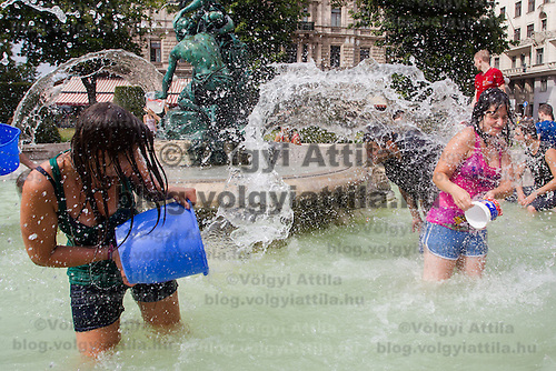 Girls splash water on each other in a public water fight in a fountain in central Budapest, Hungary on August 25, 2013. ATTILA VOLGYI