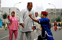 CHINA. Beijing. Acrobats warm up for a performance during the festival of Eid-al-Fitr, marking the end of Ramadan in the Muslim district of Niu jie. 2005