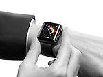 Woman hand with Apple Watch smartwatch on her wrist displaying daily activity and exercise isolated on white background
