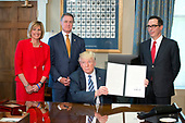 United States President Donald J. Trump holds up the order after signing the first of three Executive Orders concerning financial services at the Department of the Treasury in Washington, DC on April 21, 2017.  From left to right: US Representative Claudia Tenney (Republican of New York) US Senator David Perdue (Republican of Georgia), the President, and US Secretary of the Treasury Steven Mnuchin.<br /> Credit: Ron Sachs / Pool via CNP
