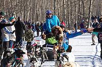 Matt Failor and team run past spectators on the bike/ski trail during the Anchorage ceremonial start during the 2014 Iditarod race.<br /> Photo by Britt Coon/IditarodPhotos.com