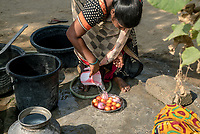 Rani barukaum, the SHG group leader uses the municipal water to wash vegetables outside her house in Ambedkar Nagar in Medak, Telangana, India.