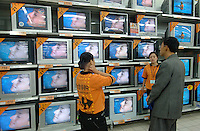 "Staff with the ""Here To Help You"" uniform serving customers in the home electronics section in popular French supermarket chain Carrefour in Chengdu, China. Third quarter sales for the French brand were up 7.3% with China being one of the major areas of growth.  Chengdu is one of western China's largest cities and the Government is encouraging investment with it's ""Go West"" campaign..24 Sep 2006"