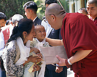 The Dalai Lama blesses recent arrivals from Tibet, including a young girl with her mother Dharamsala, northern India.<br /> Hundreds of young children walk or are smuggled over the high mountain passes of Tibet every year in hope of receiving a Tibetan education in exile. His Holiness arranges an audience with every one of them. Since the 1959 exodus from Tibet led by the Dalai Lama, more than 130,000 Tibetans in exile have fought to preserve their unique culture and identity while rebuilding their lives in the 47 Tibetan refugee settlements throughout India and Nepal. In this sense, Tibetan refugees have managed more than mere survival; they have created a Tibet in exile that is in some ways more truly Tibetan than their occupied homeland.