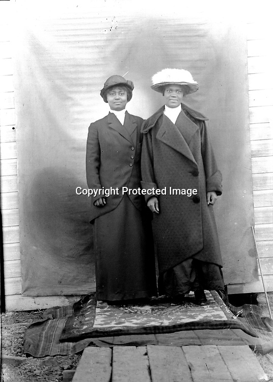 NEW WINTER COATS. The day only appears chilly--these young women are intent on showing off their winter finery. Image LB069 depicts the same pair, probably on the same day, looking comfortable in skirts and blouses. Their identities have not been recovered<br /> <br /> Photographs taken on black and white glass negatives by African American photographer(s) John Johnson and Earl McWilliams from 1910 to 1925 in Lincoln, Nebraska. Douglas Keister has 280 5x7 glass negatives taken by these photographers. Larger scans available on request.