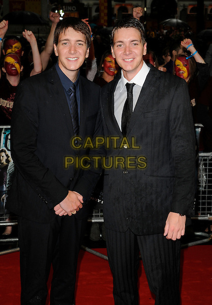 "JAMIE PHELPS & OLIVER PHELPS.The World Premiere of ""Harry Potter and the Half-Blood Prince"" at the Odeon cinema, Leicester Square, London, England. .July 7th 2009. .Half Blood half length black blue suit james pinstripe twins brothers siblings family navy 3/4.CAP/CAN.©Can Nguyen/Capital Pictures."