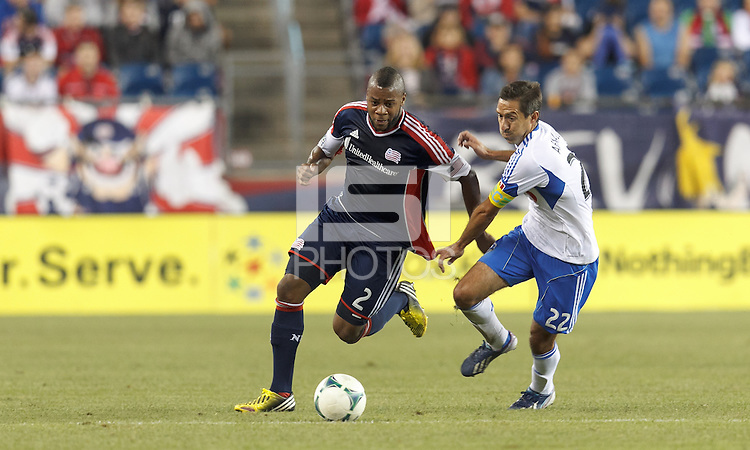 New England Revolution defender Andrew Farrell (2) works to clear ball as Montreal Impact midfielder Davy Arnaud (22) pressures. In a Major League Soccer (MLS) match, Montreal Impact (white/blue) defeated the New England Revolution (dark blue), 4-2, at Gillette Stadium on September 8, 2013.