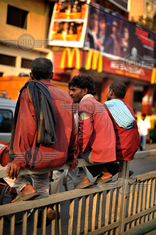 Baggage porters wait for work outside a McDonald's restaurant in Chandni Chowk in Old Delhi.