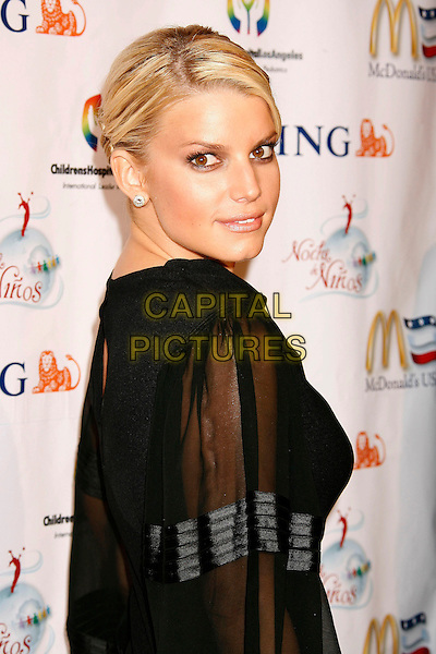 JESSICA SIMPSON.2nd Annual Noche de Ninos Gala benefiting Children's Hospital Los Angeles held at the Beverly Hilton Hotel, .Beverly Hills, California, USA,.07 October 2006..portrait headshot black dress sheer sleeved looking back over shoulder.Ref: ADM/RE.www.capitalpictures.com.sales@capitalpictures.com.©Russ Elliot/AdMedia/Capital Pictures.