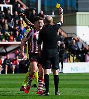 Lincoln City's Shay McCartan is shown a yellow card by referee Nicholas Kinseley<br /> <br /> Photographer Chris Vaughan/CameraSport<br /> <br /> The EFL Sky Bet League Two - Lincoln City v Cheltenham Town - Saturday 13th April 2019 - Sincil Bank - Lincoln<br /> <br /> World Copyright &copy; 2019 CameraSport. All rights reserved. 43 Linden Ave. Countesthorpe. Leicester. England. LE8 5PG - Tel: +44 (0) 116 277 4147 - admin@camerasport.com - www.camerasport.com