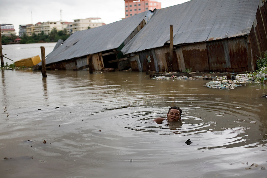 A Boeung Kak Lake man swims in the lake while attempting to fix a wooden walkways which was submerged due to heavy flooding at the lake in central Phnom Penh, Oct 11, 2010. More than 4,000 families will be evicted from their homes as part of the 133-hectare Boeung Kak Lake development project which is being carried out by Shukaku Inc.