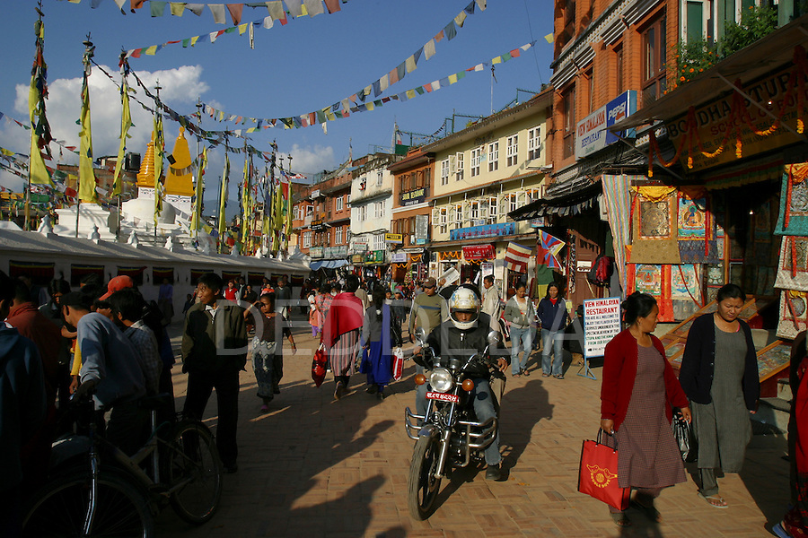 Crowds of people walk around the famous and sacred buddhist Bodhnath (or Boudhanath) Stupa in Kathmandu, Nepal..