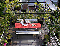 Children play at the table on the terrace. Plants have been grown up the support to create a more private outdoor space