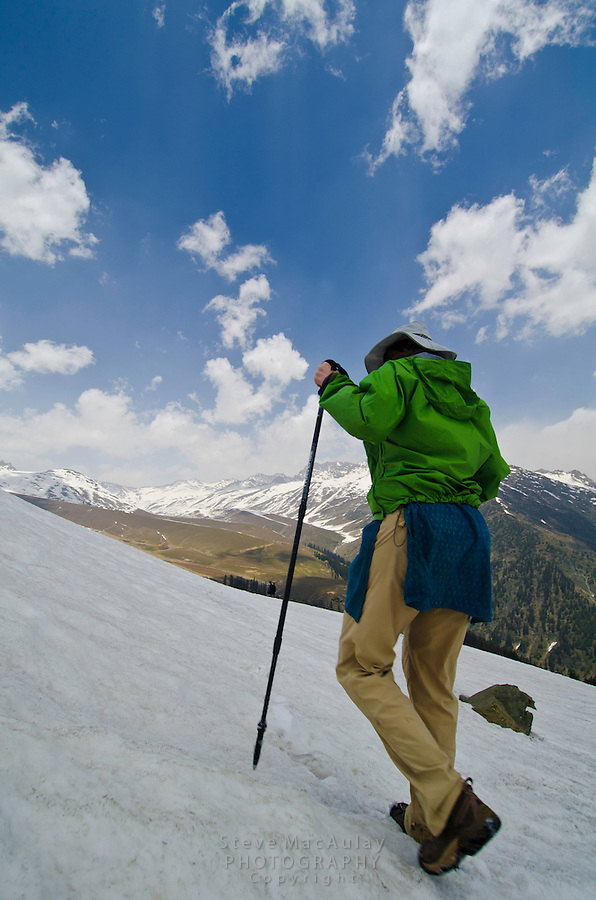 Female trekker walking on snow slope, Western Himalayan Mountains, Kashmir, India..