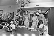 Miami, FL - May, 1976 <br /> Author Marabel Morgan displays how to properly serve a salad to one&rsquo;s husband. Morgan once famously recommended that women greet their husbands at the front door wearing nothing but &lsquo;saran wrap&rsquo;<br /> Miami, Floride, mai 1976.<br /> Marabel Morgan va donner des le&ccedil;ons pratiques chez elles &agrave; ses lectrices, il faut savoir plaire et satisfaire son mari. Elle conseillera aux femmes d&rsquo;attendre leurs maris &agrave; la porte habill&eacute;e d&rsquo;une simple feuille de cellophane.