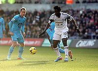 Wednesday, 19 January 2014<br /> Pictured: Wilfried Bony of Swansea (R) takes a shot which hit the post, he is marked by Christian Eriksen of Tottenham (L)<br /> Re: Barclay's Premier League, Swansea City FC v Tottenham Hotspur at the Liberty Stadium, south Wales.