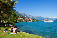 CHE, SCHWEIZ, Kanton Bern, Berner Oberland, Oberried am Brienzersee: Paar in Badekleidung auf Liegewiese, im Hintergrund ein Ausflugsschiff | CHE, Switzerland, Bern Canton, Bernese Oberland, Oberried at Lake Brienz: ecouple in bathing suits, background an excursion boat