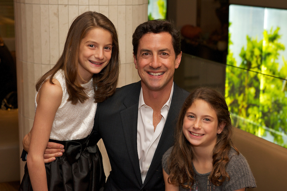 A dad posing with two daughters at a Bat Mitzvah in NYC.