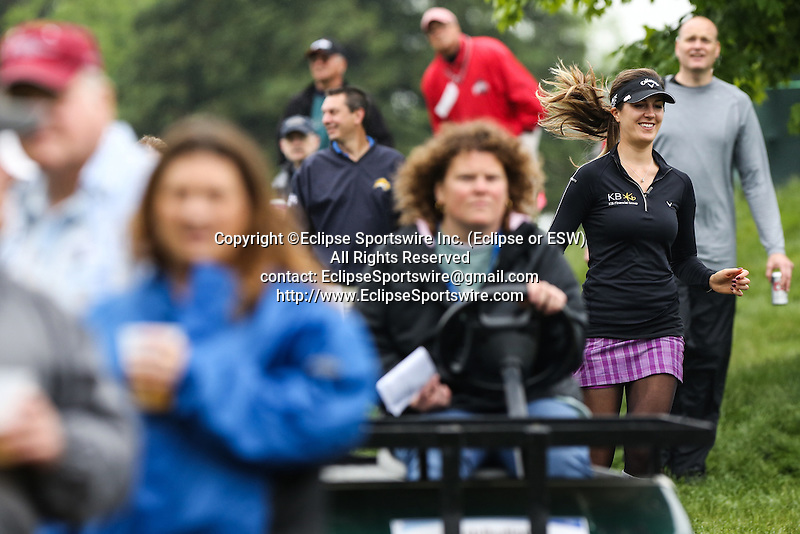 German Sandra Gal (right) runs around fans to get to the ninth tee at the LPGA Championship at Locust Hill Country Club in Pittsford, NY on June 7, 2013