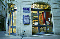 Wine shop in the old town in Bordeaux, called Cousin, on the Place du Parlement, uplit light interior and dusk outside, with a street sign saying Rue de Pas Saint Georges. Bordeaux City, Bordeaux Gironde Aquitaine France Europe  Bordeaux Gironde Aquitaine France Europe