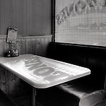A pictorial scene of the empty corner booth in a restaurant, as window lettering casts a shadow on the tabletop.