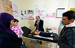 Dr. Husein Mady examines a Syrian refugee child in a clinic in Kamd El Loz, in Lebanon's Bekaa Valley, as the boy's mother and father look on. Run by the Amel Association, the clinic's work with refugees is supported by International Orthodox Christian Charities, a member of the ACT Alliance..