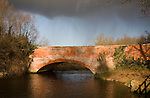 Red brick bridge crossing River Deben, Ufford with rain and storm clouds, Suffolk, England