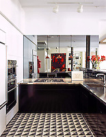 This custom kitchen floor features Christopher 2, a handmade mosaic shown in honed Nero Marquina, Thassos, Carrara, and Bardiglio, part of the Illusions&reg; collection by Sara Baldwin for New Ravenna.<br />
