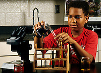 Black boy student age 13 in Eighth grade learning science at lab des