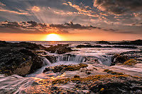 Golden sunset and water flow at the drains along the Kona coastline of the Big Island of Hawai'i.