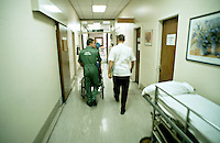 Paramedic ambulance crew rushing a patient in a wheelchair through to the accident and emergency department of a hospital.