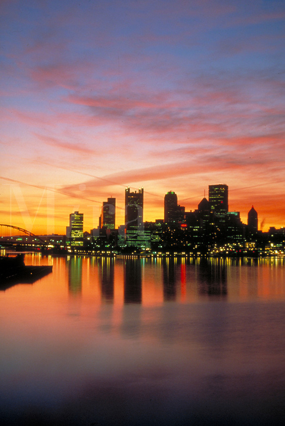 Pittsburgh's skyline is brilliant with the multi-colored sky and reflections on river. Pittsburgh Pennsylvania United States skyline.