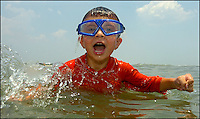 A young boy (model released) plays while at the beach on the Atlantic ocean. Photo taken on Sullivan's Island, near Charleston, South Carolina beach on the Atlantic Ocean, but could represent a beach scene anywhere.