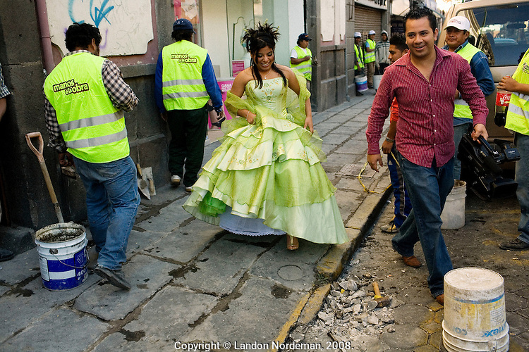 Puebla, Mexico - DEC 3: Karla Delgado Suarez's mother hired videographer Aldo Abarca to shoot a video portrait of her daughter at various locations around the city in celebration of her upcoming quinceanera on Wednesday, December 3, 2008, in Puebla, Mexico. Here, they walk by construction workers on the sidewalk en route to a location to begin the video. The video portrait is a very popular item for young women to want for their quinceanera--after they've chosen a dress, that is. (Photo by Landon Nordeman)