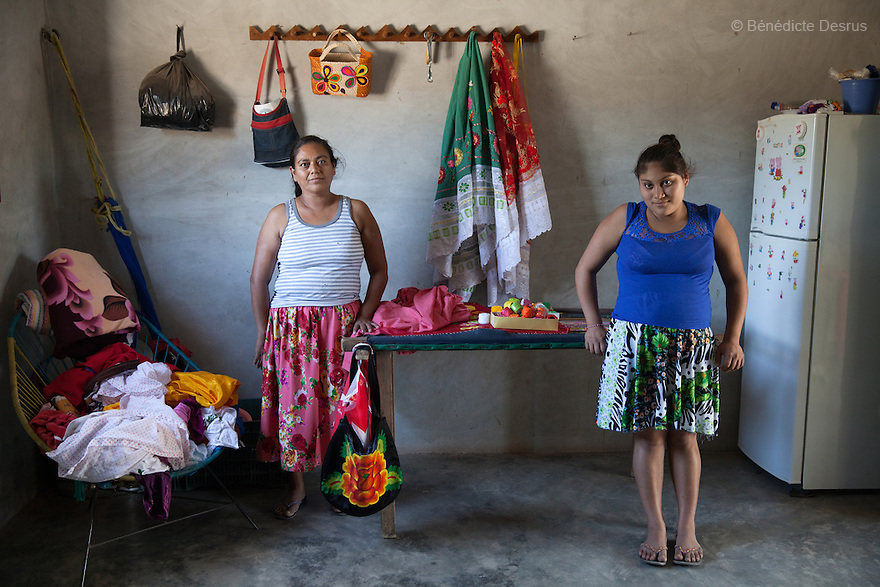 """Xhunaxhi Rosalía Santiago López (R) portrayed with her mother Antonia López Guerra (L) at their home in Santa María Xadani, Oaxaca, Mexico on February 18, 2016. Xhunaxhi – her name means """"virgin"""" in Zapotec – is 14 and lives with her 18-year-old partner and her mother, who had her own first child aged 17, in the town of Santa María Xadani in the southern Mexican state of Oaxaca. Xhunaxhi, who speaks little Spanish, is painfully shy and childlike and punctuates her comments with giggles. She is five months pregnant, but seems not to really understand – she has to ask her mother when her baby is due. She left school at 10 to travel with her family to Tepic, in the western state of Nayarit, for six-month stints working cutting sugar cane. She met her boyfriend last year, keeping the relationship secret from her mother, and was """"stolen"""", according to the Zapotec tradition. She plans to marry legally at 18. While Mexico has outlawed marriage under the age of 18, many young girls become unofficial wives and mothers much earlier. In Juchitán, teenage pregnancy is expected, even prized. Mexico ranks first in teenage pregnancies among the member countries of the Organization for Economic Co-operation and Development(OECD). Photo by Bénédicte Desrus"""