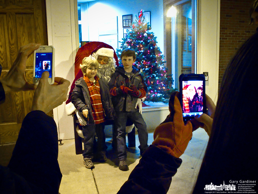 A pair of mothers use their cell phone camera to take a photo of their children sitting on Santa's knee after his arrival at the Christmas Tree lighting ceremony.