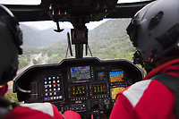 "Switzerland. Canton Ticino. Quartino ( Rivera). A Rega Agusta AW109 SP Grand ""Da Vinci"" helicopter on its way to rescue an elderly man suffering from a heart problem. Approaching flight to the accident scene. Rain on the the cockpit window. All Rega helicopters carry a crew of three: a pilot Corrado Sasselli (R), an emergency physician, and a paramedic Paolo Menghetti (L) who is also trained to assist the pilot for radio communication, navigation, terrain/object avoidance, and winch operations. The name Rega was created by combining letters from the name ""Swiss Air Rescue Guard"" as it was written in German (Schweizerische Rettungsflugwacht), French (Garde Aérienne Suisse de Sauvetage), and Italian (Guardia Aerea Svizzera di Soccorso). Rega is a private, non-profit air rescue service that provides emergency medical assistance in Switzerland. Rega mainly assists with mountain rescues, though it will also operate in other terrains when needed, most notably during life-threatening emergencies. As a non-profit foundation, Rega does not receive financial assistance from any government. The AgustaWestland AW109 is a lightweight, twin-engine, helicopter built by the Italian manufacturer Leonardo S.p.A. (formerly AgustaWestland, Leonardo-Finmeccanica and Finmeccanica). Leonardo S.p.A is an Italian global high-tech company and one of the key players in aerospace. In close collaboration with the manufacturer, the Da Vinci has been specially designed to cater for Rega's particular requirements as regards carrying out operations in the mountains. It optimally fulfills the high demands made of it in terms of flying characteristics, emergency medical equipment and maintenance. Safety, performance and space have been increased, and maintenance and noise emissions reduced. 10.09.2017 © 2017 Didier Ruef"
