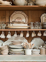 Traditional tableware is neatly arranged on shelves in a wooden cupboard.