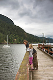 CANADA, Vancouver, British Columbia, father and daughter lean on a railing on a dock on Gambier Island, in the Howe Sound