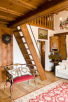 A cuckoo clock hangs above a salvaged chariot seat beneath a ladder staircase leading to the mezzanine