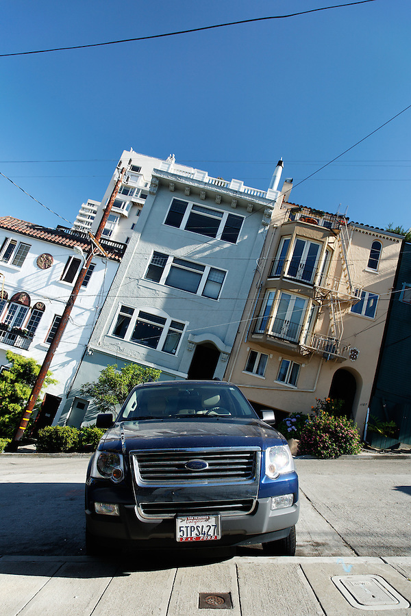 Ford SUV parked on Filbert Street's steep hill, camera tilted along slope of road, San Francisco, California, USA, North America