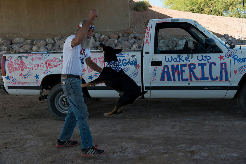 Steve Myers, a supporter of Cliven Bundy who traveled from Oregon, plays with his dog in front of his truck, adorned with anti-government slogans.