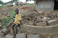 Ajok Jacob plays among abandoned and demolished huts that lie among still-occupied homes in Agwang Camp in Lira District in Northern Uganda. While many neighbors have returned to their villages in the wake of a September 2006 ceasefire in the Northern Uganda conflict, some are physically unable to rebuild. The conflict with the Lord's Resistance Army had forced as many as two million people into camps across northern districts for as many as 20 years. The LRA and Ugandan government have  observed a ceasefire while engaged in peace talks to end the conflict. As a result many residents of camps for the internally displaced have been slowly returning to their villlages to begin again.  (Rick D'Elia)