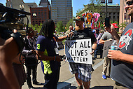 "Cleveland, OH - July 20, 2016: A man holding a sign that reads, ""Not All Lives Matter,"" is interviewed by a member of NewsOne media as he protests in Public Square during the Republican National Convention in downtown Cleveland, Ohio, July 20, 2016.  (Photo by Don Baxter/Media Images International)"