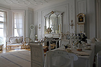 The large panelled living/dining room is lit by floor-to-ceiling windows and elegantly furnished with antique Swedish pieces