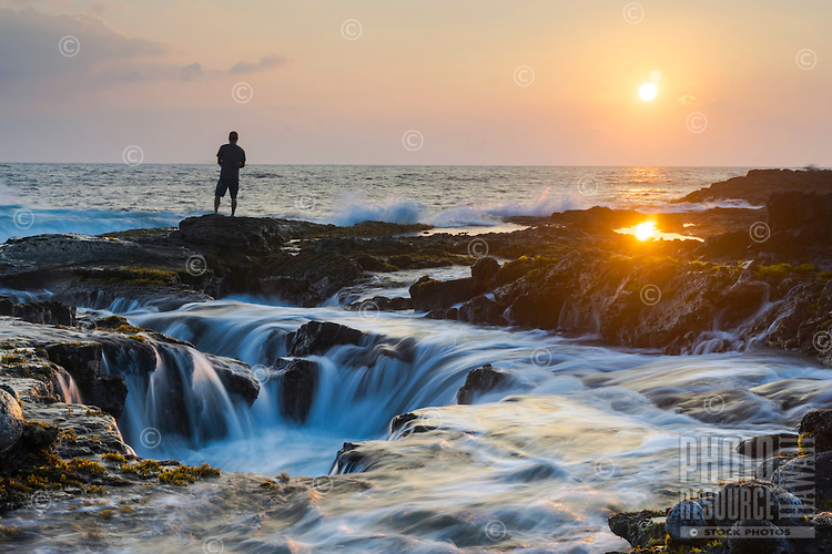 A fisherman on the rocky Big Island coastline during sunset.