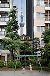 Tokyo, June 29 2013 -Kids playing in front of an old house in the Asakusa area, with the Tokyo Skytree in the background.